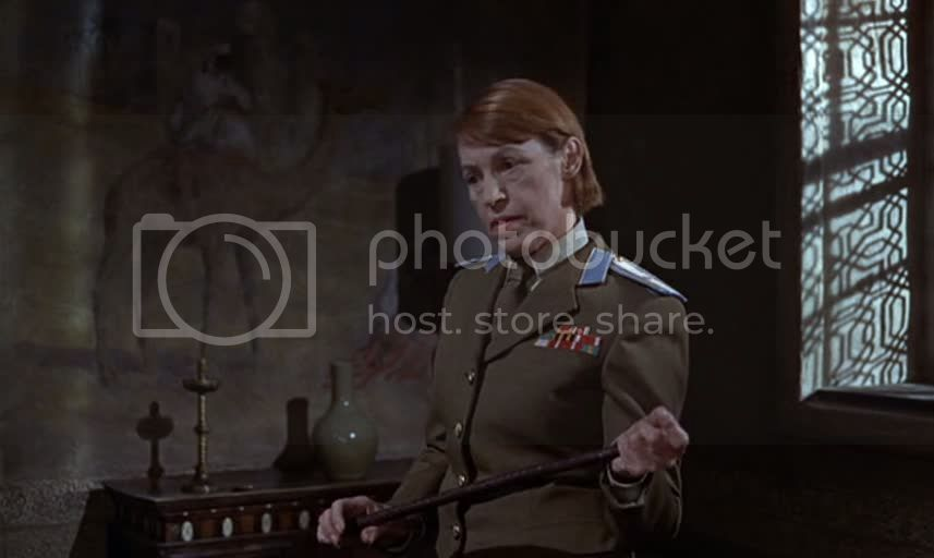 Lotte Lenya as Klebb dressed in military uniform, holds a swagger stick, the tip resting in her other hand in an attitude of slightly camp menace.